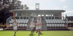 Boys running out of Sports Pavilion ready to play rugby