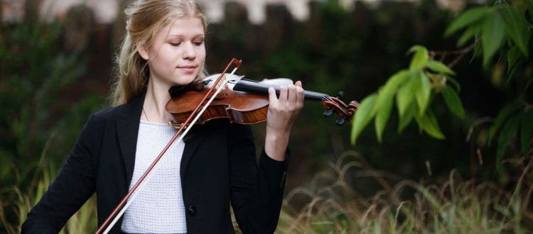 Student playing the violin in the garden