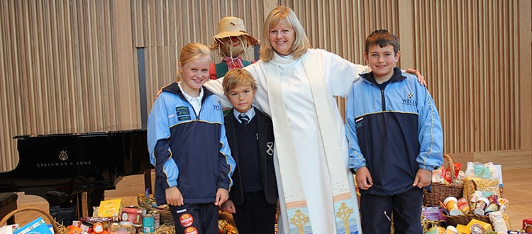 Chaplain and a group of pupils at the Harvest Festival