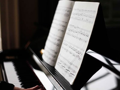 Piano with hands and a book.