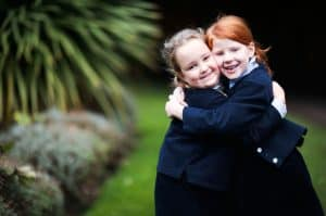 Two little girls giving one another a hug