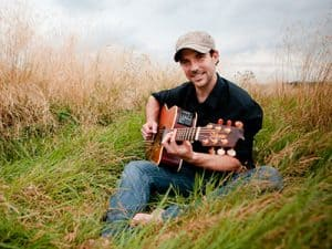 Sam Wedgwood playing guitar outside