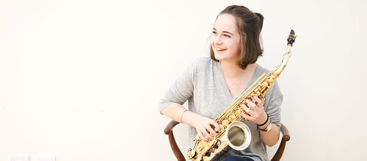 Girl holding saxophone and smiling