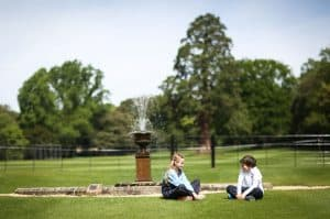 Junior School pupils sitting by the fountain on Cedars Lawn